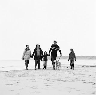 Une famille qui se balade main dans la main sur la page.