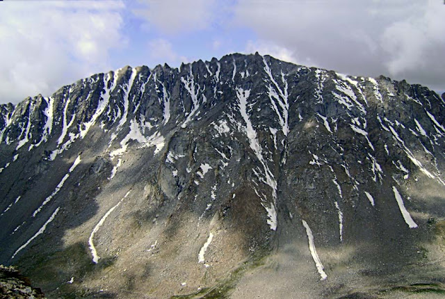 snow in stripes coming down a mountain