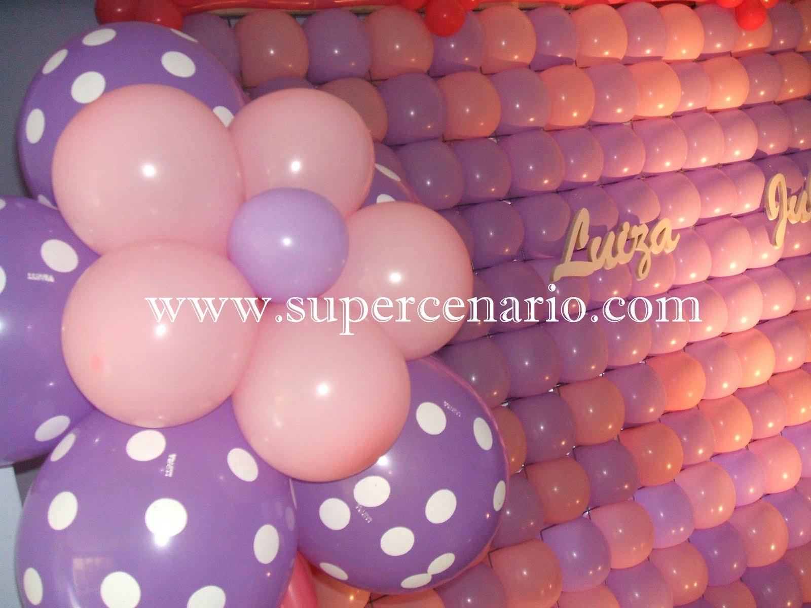 Flores com balões de poá nas laterais da mesa deixam o conjunto