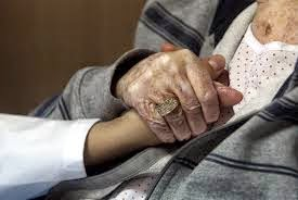 Dar la mano un sanitario a un enfermo