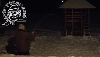 Szöveg: Locsolni kell este... Kép: Barna dzsekis kötött sapkás férfi slagból ereszti a vizet a ledöngölt havú földre.