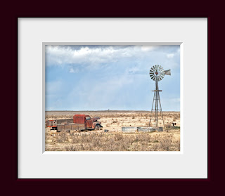 an abandoned old truck resting next to a prairie windmill on the High Plains of Colorado