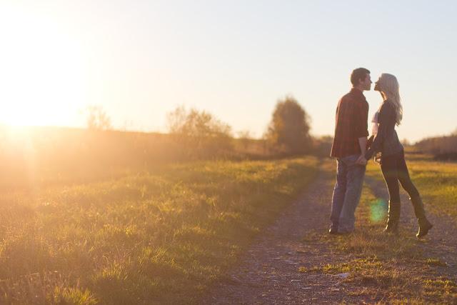couple walking down path kissing