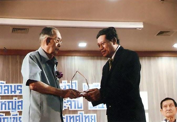 เจียวต้าย (ซ้าย) รับรางวัล นราธิป ประจำปี ๒๕๕๖ เมื่อ ๒๕ มกราคม ๒๕๕๗