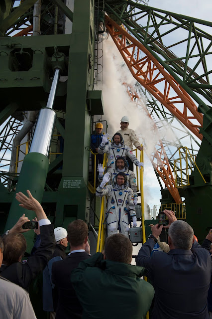 Soyuz TMA-18M crew members ESA astronaut Andreas Mogensen, Kazakh cosmonaut Aidyn Aimbetov, and Roscosmos spacecraft commander Sergei Volkov, greeting audience at the launch pad in Baikonour, Kazakhstan, on 2 September 2015. ESA–S. Corvaja