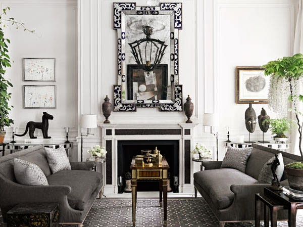 Gray living room with dueling sofas and a black and white fireplace with a large mirror on the matel