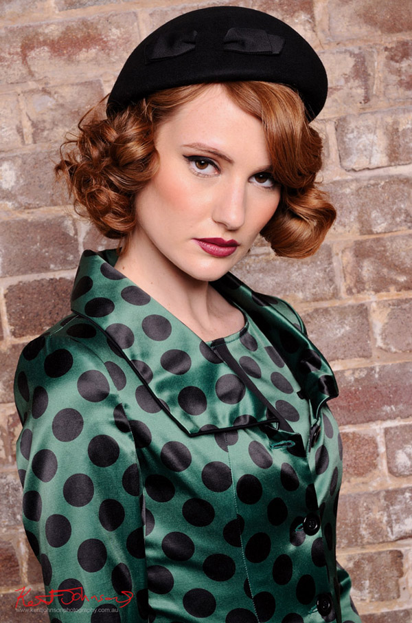 Green satin jacket and blouse worn with a black beret with black satin bow, tight shot of model - Vintage Fashion