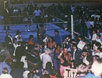 Jimmy Hart leads Hart Foundation from the ring with their title belts in Newmarket Ontario in 1987.