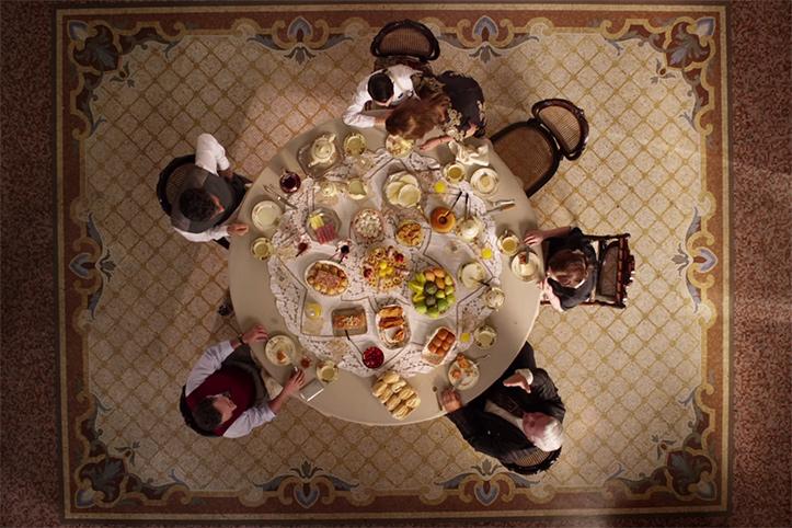 Cena do filme Infância de Domingos Oliveira filmada de cima, onde a família está à mesa de café da manha