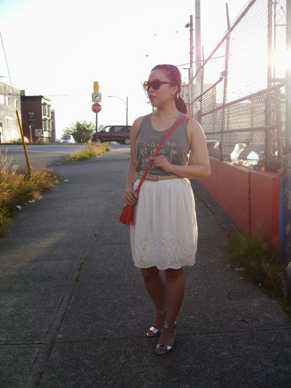 Grey racerback tank, white eyelet skirt, and red crossbody bag