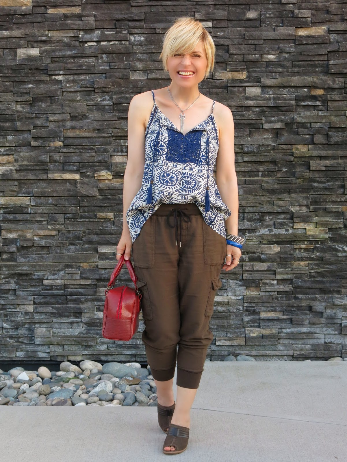 styling slouchy cargo pants with a peasant-style tank top and a red box bag