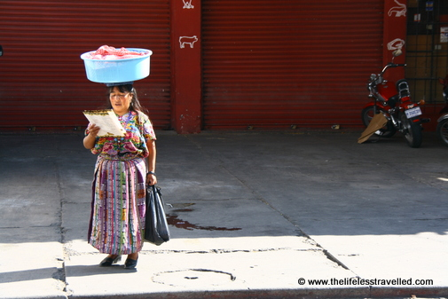 Guatemalan woman with a large tub balanced on her head, while she reads a menu.