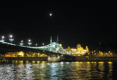 Illuminated bridge and building with moon up above