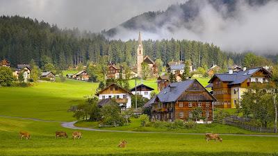 Pueblo campestre junto a las montañas con granjas