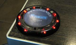 [Image: Photo of a saucer-shaped device sitting on the edge of a table, with red LEDs all around it. It has a label sticker with a logo that is redacted from the photo.]