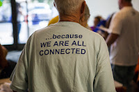 "back of a volunteer.  T-shirt reads: ""...because we are all connected."""