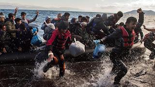 Πρόσφυγες χειροκροτούν μετά από την επιτυχή άφιξη στη Λέσβο.