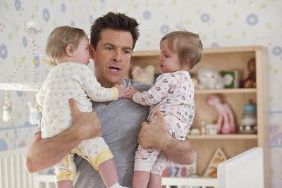 Vemos una escena de la película El Cambiazo donde Jason Bateman tiene a dos niños en brazos.