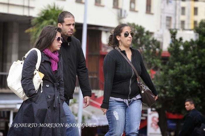Transeúntes vestidos con bufandas, chaquetas pesadas y guantes, prendas que no suelen usarse en Cuba, pasean  bajo las temperaturas mínimas provocadas por el primer frente frio del año en La Habana, el 7 de enero de 2014.