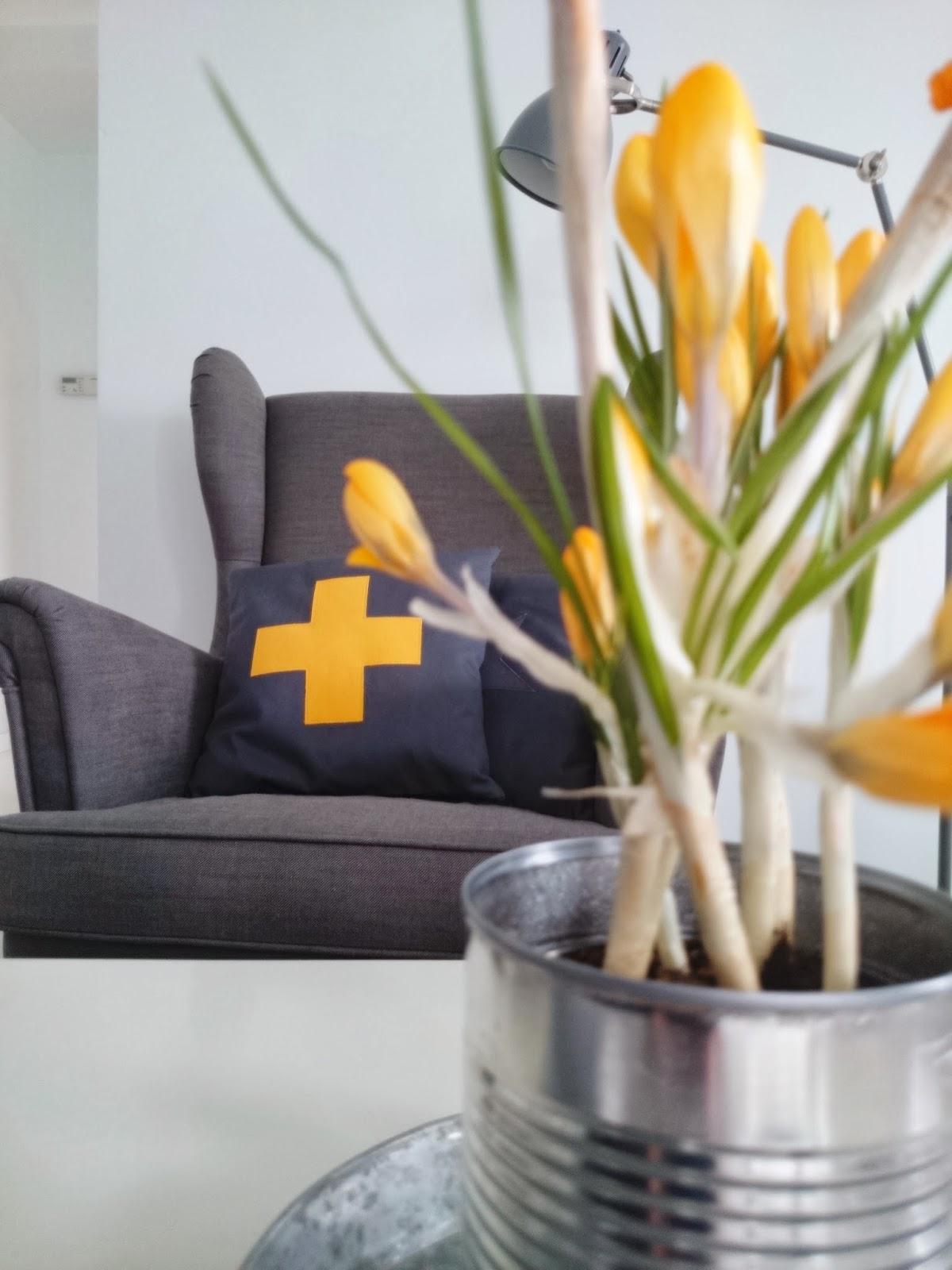 Szary fotel uszak, poduszka żółty plus, żółte krokusy, salon  z żółtymi akcentami
