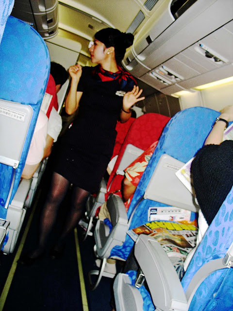 stewardess in aisle of aeroplane