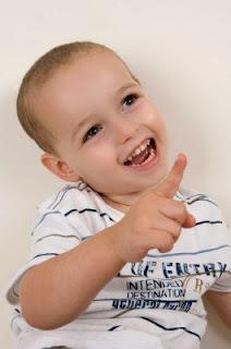 Niño señalando. Niño diciendo palabrotas y riendo.