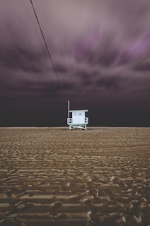 lone white lifeguard stand on wet beach with dark sky and storm clouds behind