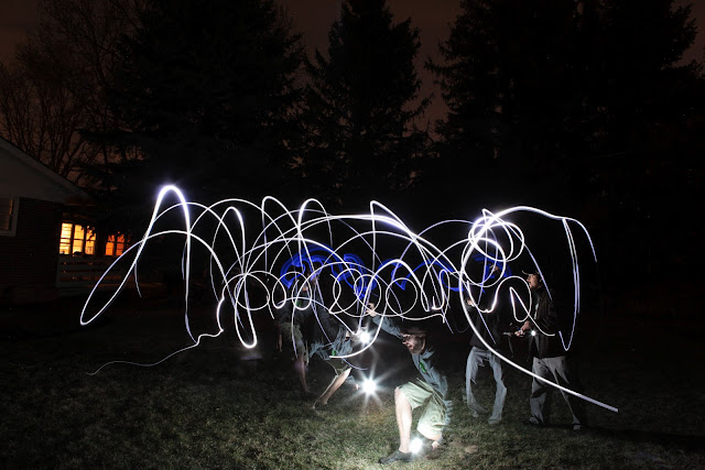 Light painting in a backyard while also popping a Canon Speedlite with big trees as a backdrop.