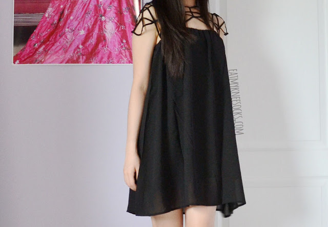Romwe's uniquely-designed black caged shift dress has an edgy cutout neckline and flowy skirt.