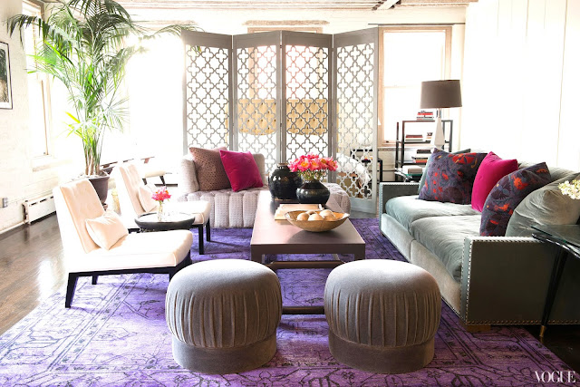 Living room in Zani Gugelmann's New York City loft with a purple Persian rug, grey sofa, pink and grey accent pillows and a room divider