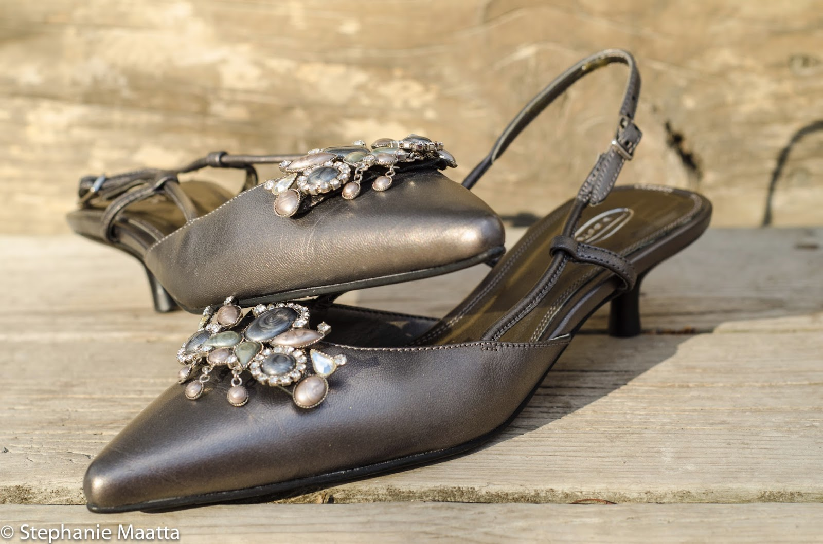image of a pair of shoes with jeweled brooches on wooden stairs