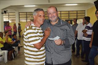 Edir Luiz de Souza, comerciante aposentado, recebe das mãos do prefeito Márcio Catão o cheque referente à indenização