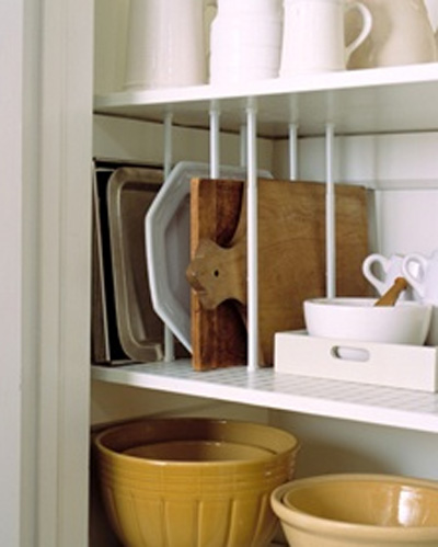 Perfect Tip Maximize the use of shelving by creating dividers to store pans and trays on their side This was created using curtain tension rods