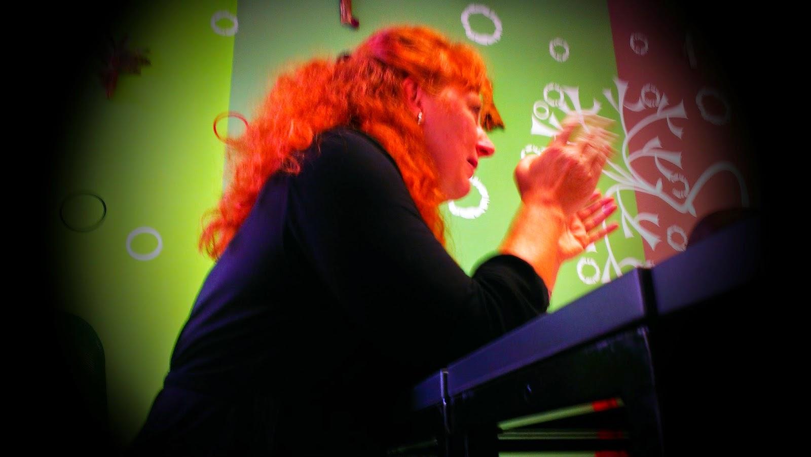 žena za stolem vykládá a má vztažené ruce v gestu výkladu