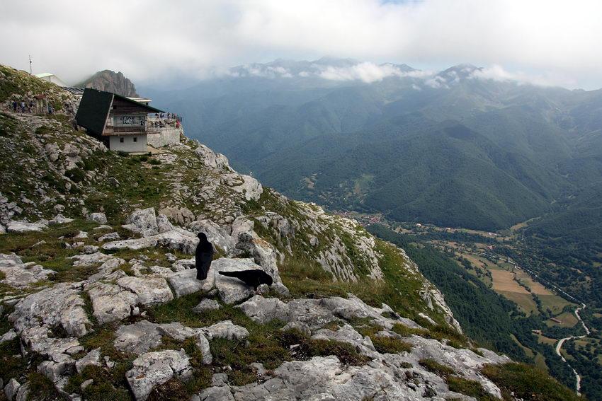 Paisagem de montanha com os picos cobertos por nuvens. Em Baixo, no vale, vegetação e uma estrada serpenteante