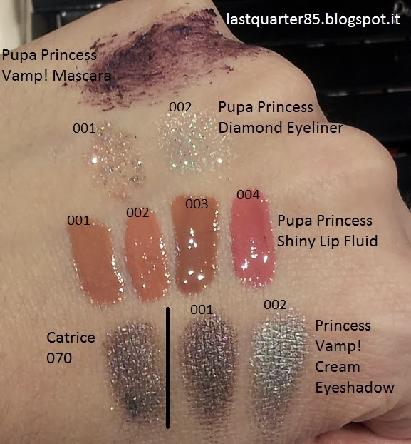 Swatch prodotti Pupa Princess: dall'alto verso il basso Pupa Princess Vamp Mascara, Diamond Eyeliner, Shiny Lip Fluid e Cream Eyeshadow.