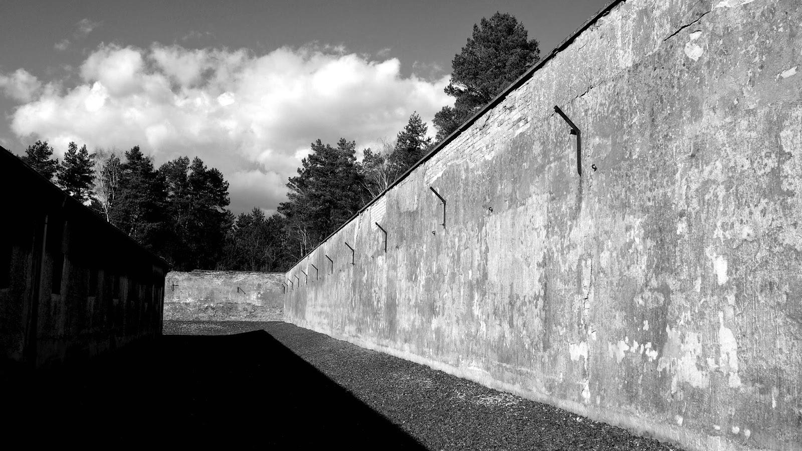 Rechts eine Mauer mit Befestigungen für Stacheldraht. Links ein Werkstattgebäude, eingeschossig.