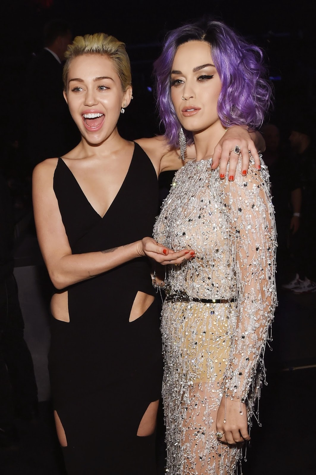 Miley Cyrus shows off cleavage in a plunging black gown at the 57th Annual Grammy Awards in LA
