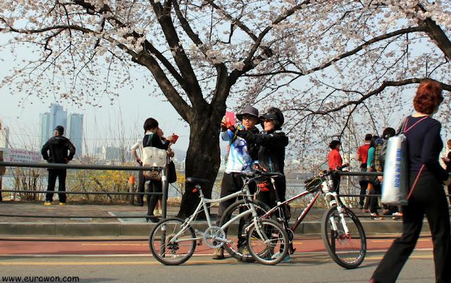 Pareja de ciclistas tomándose una foto con las flores