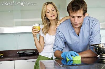 الرجل العصري عند المرأة الألمانية هو من يساعد في أعمال البيت - young_woman_laughing_at_man_using_sponge_in_kitchen