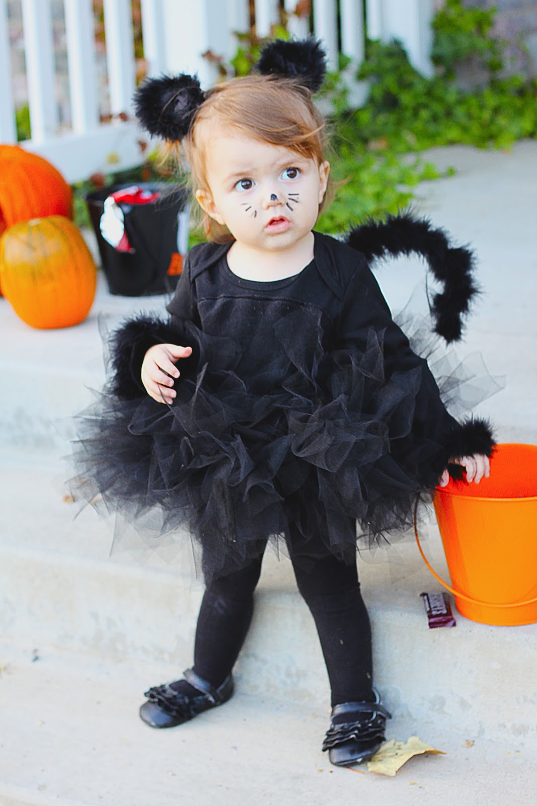 To add a tail to your black cat costume, cut apart a wire hanger, bend as desired, and wrap with a black feather boa, hot-gluing as you go. Tip: The makeup can be as minimal or as detailed as you like.