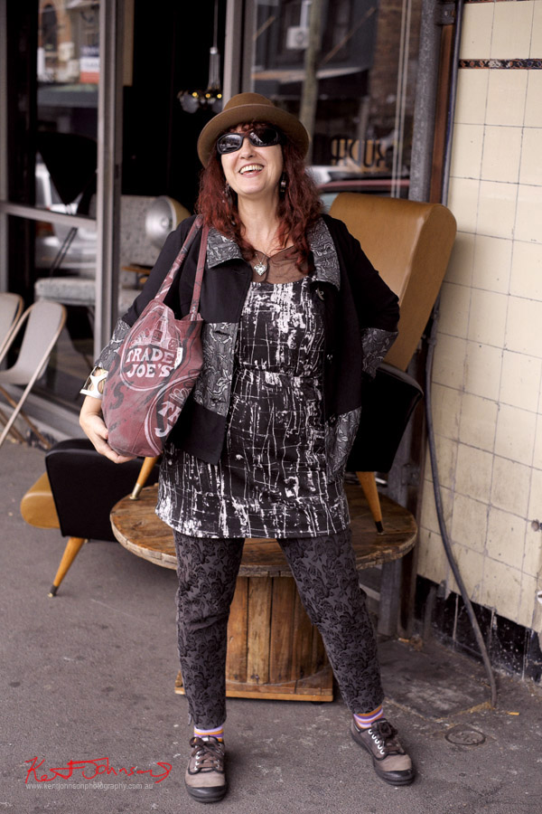 Didi working a Black white and grey patterned outfit, pants dress and jacket with brown Akubra Fedora, Trader Joe's tote bag.