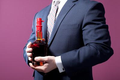 mężczyzna w garniturze trzymający butelkę whisky