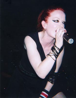 Garbage lead singer and all-round sex goddess Shirley Ann Manson holds a microphone and leads forward as she sings live