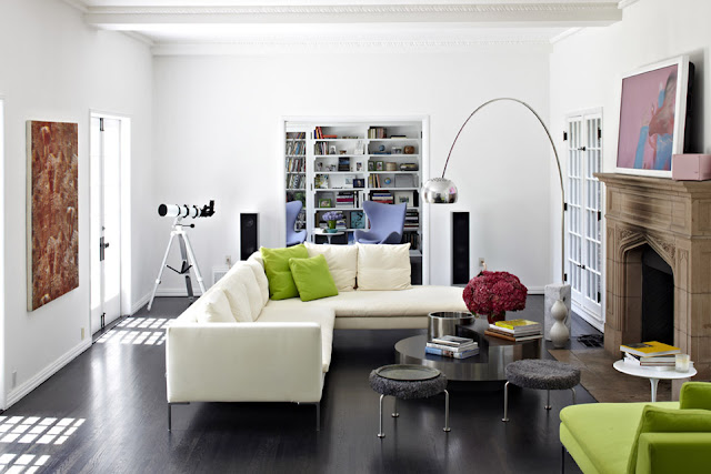 A modern living room with a silver 1962 Arco Lamp by Castiglioni, white sectional sofa, dark wood floor, a mirrored coffee table, a telescope, and a green armchair with a white round coffeetable