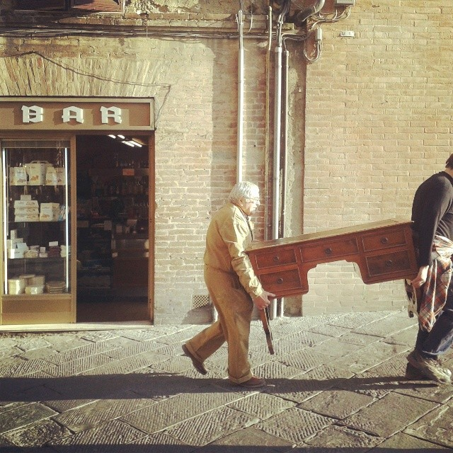 Two artisans carrying an antique desk through Siena's town center