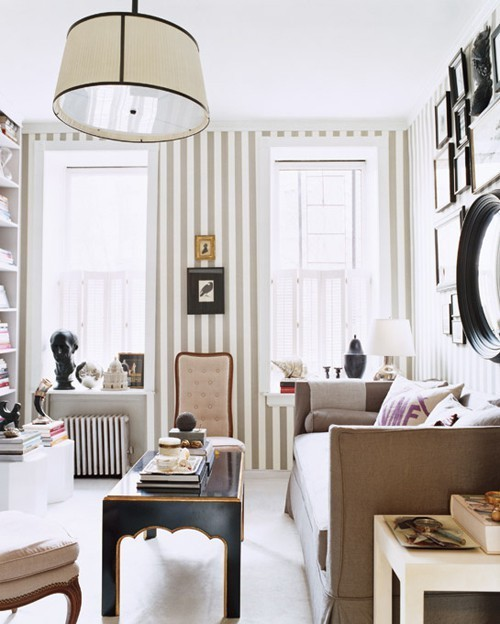 Living room with a large pendant light, neutral armchair, black coffee table and beige and white striped walls