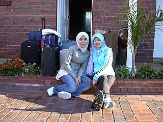 Two musilm girls take a picture before they move into their new house