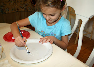 "Tessa began her ""Quick and Sweet Ziggurat"" by arranging the bottom layer of sugar cubes on a disposable plate, drawing about its perimeter, removing the cubes, then painting with glue within the marked area. We later discovered that it is more efficient to simply dip the sugar cubes into a puddle of glue."