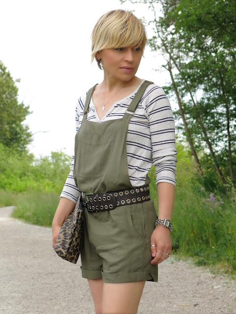 styling olive shortalls with a striped henley top and a wide belt